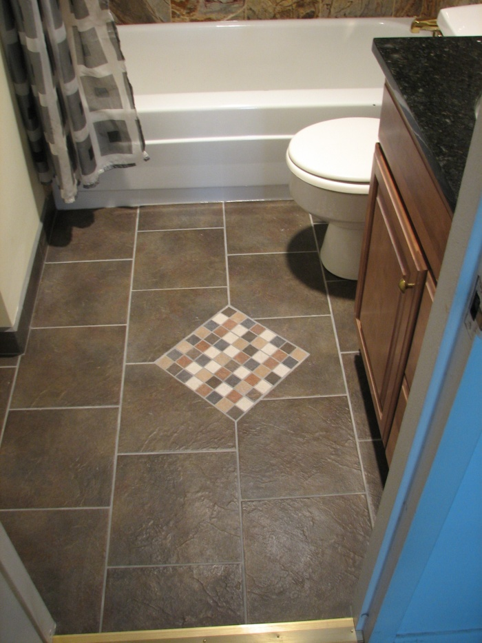 The bathroom flooring matches beautifully to the bathtub tile, and has